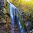 Beautiful waterfall in a rays of evening sun — Stock Photo