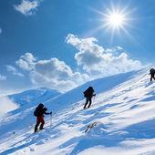 Hiker upwards a snow slope — Stock Photo