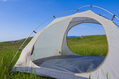 White touristic tent among a green fields — Stockfoto