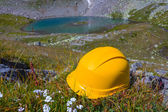 Yellow helmet on a stone in a mountains — Stock Photo