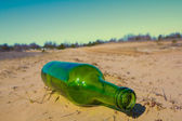 Green bottle on a sand — Stock Photo