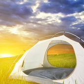 White touristic tent among a field at the sunrise — Stock Photo