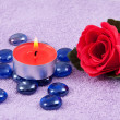 Red rose and aroma candle on the towel — Stock Photo