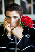 Handsome Man left with roses — Stock Photo