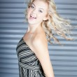Dancing beautiful blond woman with steel door background — Stock Photo
