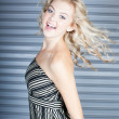 Dancing beautiful blond womwith steel door background — Stock Photo #13884608