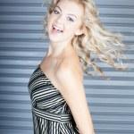Dancing beautiful blond woman with steel door background — Stock Photo