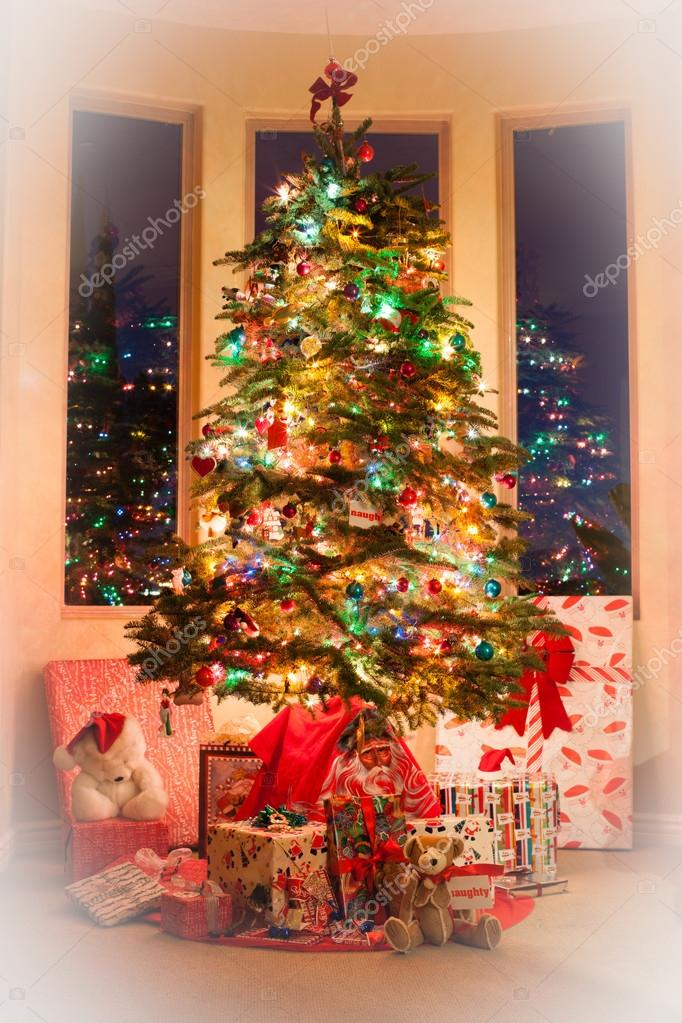 Beautiful Christmas tree decorated with gifts from Santa at sunrise on Xmas day  Stock Photo #14080152