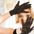 Beautiful woman framing her blue eyes with Black gloves — Stock Photo