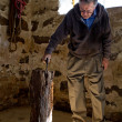 Senior Man grabbing his Axe from in the barn — Stock fotografie