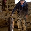 Senior Man grabbing his Axe from in the barn - Stockfoto