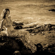 Beautiful Mermaid on Lava Rocks black and white image - Stock Photo
