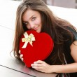 Beautiful young woman with long hair and a heart — Stock Photo