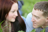 Man looking deeply in love in the meadow with his woman — Stock Photo