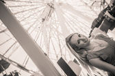 Young pretty woman in front of a Ferris wheel in B & W — Stock Photo