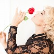 Beautiful Blonde woman and a rose - Stock Photo
