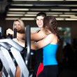 Thre friends exercising at the gym on stair steppers - Stock Photo