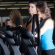 Thre friends exercising at the gym on stair steppers — Stock Photo