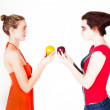 Royalty-Free Stock Photo: Beautiful women comparing oranges to apples