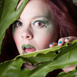 Surprised Beautiful amazon Woman in leaves  with fun green makeu - Stock Photo