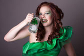 Pretty red headed woman drinking from a Mug with a shamrock on i — Stock Photo