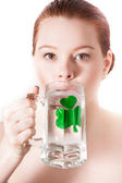 Pretty young woman drinking from a Mug with a shamrock on it — Stock Photo