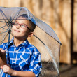 Young boy in a sun shower with umbrella — Stock Photo