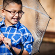 Smiling young boy in the rain with umbrella — Stock Photo