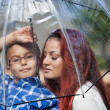 Mother and son in the rain with umbrella — Stock Photo