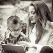 Mother and son reading from a touch pad black and white sepia to — Stock Photo