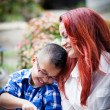 Mother and son laughing while together on a touch pad — Stock Photo