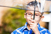 Young boy in the rain with umbrella — Stock Photo