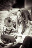 Mère et fils de lecture à partir d'un touch pad noir et blanc sépia à — Photo