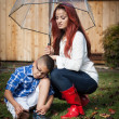 Latin Mother and son in the rain with umbrella in spring for Mot — Stock Photo