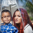 Latin Mother and son in the rain with umbrella in spring for Mot — Stock Photo #21251871