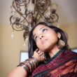 Beautiful Indian woman under a chandelier - Stock Photo