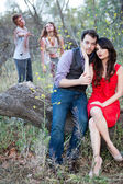 Romantic Couple on a log with Zombies — Stock Photo