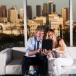 Stock Photo: Mature couple at night working with skyline