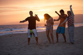 Friends in their twenties dancing on the Beach at Sunsrt — Stock Photo