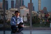 Mogna stilig affärsman på natten arbetar med skyline — Stockfoto