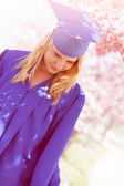 Beautiful High school Graduate under Cherry Blossoms — Stock Photo
