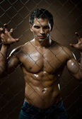Muscular guy on netting steel fence — Stock Photo