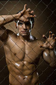 Felon man on netting steel fence — Stock Photo