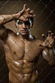 Felon man on netting steel fence — Stock Photo