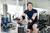 Athletic guy exercise-bicycle — Stock Photo