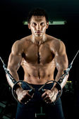Bodybuilder on sport-apparatus — Stock Photo