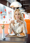 Woman drink coffee or tea with croissant — Stock Photo