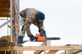 Workman with petrol-powered saw — Stock Photo
