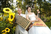 Fiancee blow the balalaika,  bridegroom play on accordion — Stock Photo