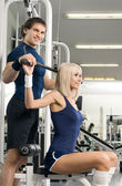 Girl and guy exercise on sport-apparatus — Stock Photo